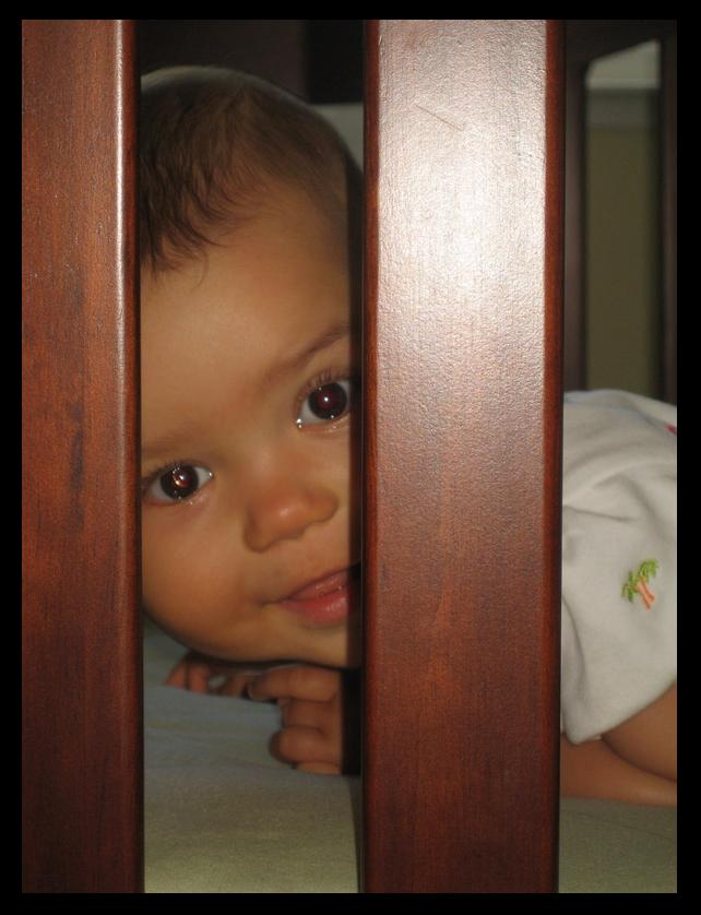 Ari peeking between crib slats