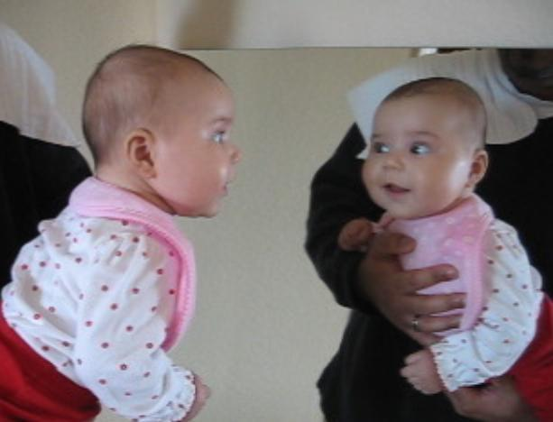 Ari smiling at herself in the mirror